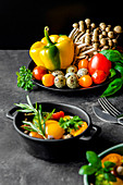 Tasty vegetable salad with tomatoes and mushrooms garnished with green basil and rosemary sprigs