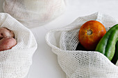 Raw potatoes and peppers in eco friendly fabric bags placed on table in kitchen