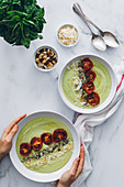 Crop unrecognizable person serving bowls with delicious avocado and apple cream soup decorated with sun dried tomatoes and toasted grated coconut with cashew nuts and fresh basil
