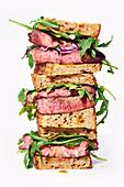 Gestapelte Rindersteak-Sandwiches mit Rucola und Senfdressing