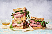 A pile of beef steak sandwich with arugula and mustard dressing against bright background