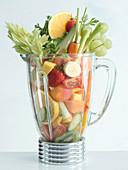 A blender full of fresh vegetables and fruit