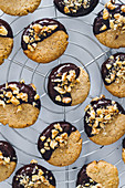 Cookies with walnuts and chocolate placed on metal tray on table in kitchen