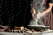 Crop anonymous male baker in apron spilling flour over baking pan with bread while working at table with ingredients