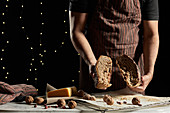 Crop unrecognizable male baker in apron cutting loaf of fresh artisan rye bread with grains