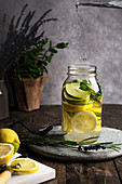 Still life of lemonade in a glass jar, placed on a wooden table