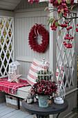 Weihnachtlich dekorierte Philosophenbank mit rotem Beerenkranz, Holzstern und dekoriertem Tischchen