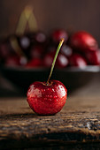Cherry, on the background bowl full of fresh cherries on wooden table against dark background