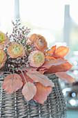 Strauß aus apricotfarbenen Ranunkeln mit Statice auf künstlichem Herbstlaub