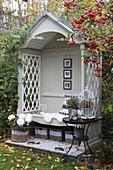 Herbstlich dekorierte Philosophenbank mit Zierapfelbaum und weißen Chrysanthemen im Korb