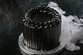 Delectable black cake placed on table in steam of liquid nitrogen in studio