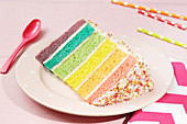 A slice of rainbow cake covered in sprinkles on a plate