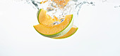 Honeydew melon falling into fresh water