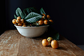 White ceramic plate with tasty natural loquat fruits on branch with fresh green leaves placed on wooden shabby desk