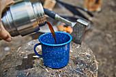 Kaffee auf dem Campingplatz in blauen Becher gießen