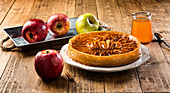 Served whole pie with apples in syrup placed on plate among fresh apples on wooden table