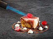 Sophisticated turkish dish made with wagyu beef fillet served on piece of pastry and garnished with chili cream sauce and yogurt with marinated onion being grilled with torch burner