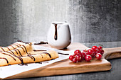 Yummy homemade pancakes or crepes with chocolate syrup served on wooden board with fresh red berries against shabby wall