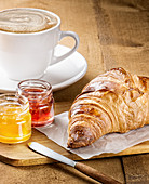 Freshly baked croissant served with fruit marmalade and cup of hot coffee with milk on wooden table