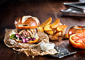 Appetizing big burger with fresh vegetables and beef patty with fried potatoes served on slate board with fries