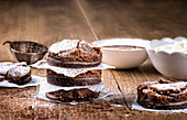 Round freshly baked brownies on table with bowls of chocolate and butter