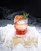 Glass with refreshing alcohol cocktail with red orange and ice garnished with fresh rosemary