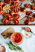 Glass pot with homemade tomato sauce placed on table next to metal tray with grilled tomatoes with garlic and rosemary