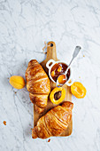 Appetizing fresh croissant served with pot of homemade apricot jam on wooden cutting board