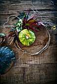 Ornamental pumpkins and autumn leaves on a rustic wooden background