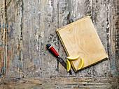 Holzbrett, Messer und Zitronenschnitze auf Holzuntergrund