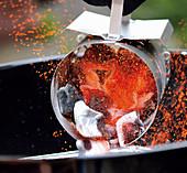 Glühende Kohl aus Anzündkamin in den Grill schütten