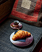 Croissant on a plate with an espresso