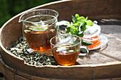 Minztee in Glaskanne und Tasse daneben getrocknete Blätter
