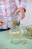 Glasfilter mit Lindenblütentee aus der Teekanne heben