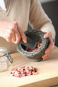 Crushing dried rose petals in a mortar