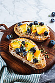 Sandwiches with homemade bread and fresh apricot and blueberries garnished with thyme