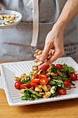 Vegetarischen Salat mit gerösteten Cashewnüssen garnieren