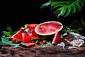 Glass of sweet fruit juice with mint on wooden table with strawberries and ripe watermelon