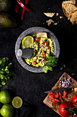 Vegetarian guacamole with tomatoes and lime garnished with fresh parsley