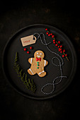 Christmas gingerbread cookie placed on tray with holiday decorations