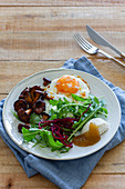 Fried egg served with mushrooms and fresh salad