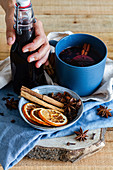 Mulled wine arranged on table with aromatic cinnamon sticks and dried oranges
