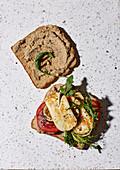 A halloumi sandwich with lentil cream with antipasti vegetables