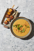 Parsnip and peanut soup with tofu skewers