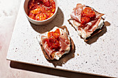 Bread topped with goat's cream cheese, ham and chutney