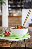 Bowl with appetizing salad and chopsticks, served with red chili pepper