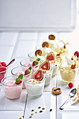Various yoghurt desserts with fruit in small glasses