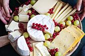 Käseplatte mit Trauben und roten Johannisbeeren auf Holzteller