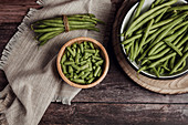 Fresh whole and cut green beans in wooden and metal bowls