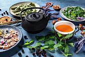 Tasse Kräutertee mit Teekanne und verschiedenen Kräutern, Früchten und Blumen